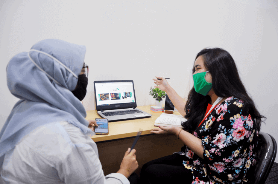 2 Females Employees of Cohub Discussing in Front of a Laptop